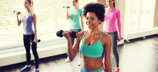 61181159 - fitness, sport, training and lifestyle concept - group of happy women with dumbbells flexing muscles in gym
